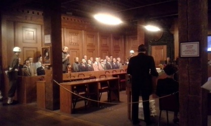 Life-size replica of a scene during the Nuremberg trials, with actual footage playing in the background.